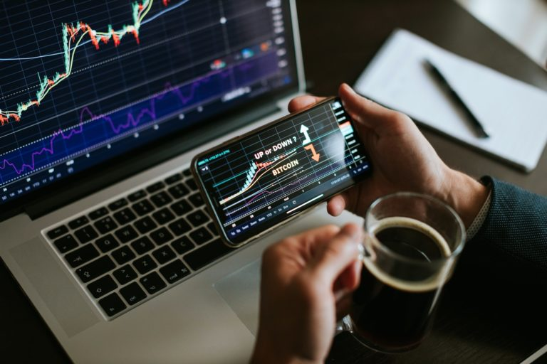 investment stockbroker predicting bitcoin price trend movement using laptop and phone