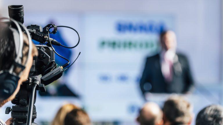 Media Event. Cameraman With Headphones Recording Speaker